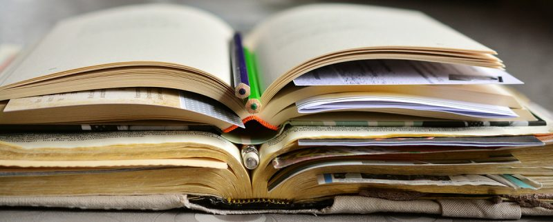 geöffnete Bücher, gestapelt mit Bleistiften und Notizzetteln